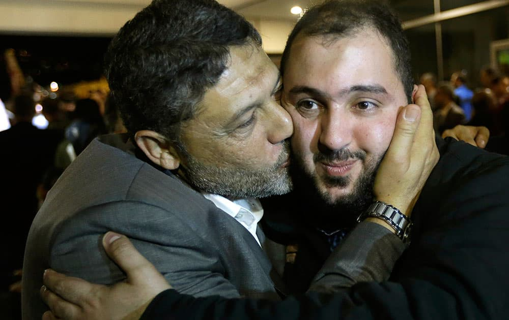 Ali Abbas, right, one of nine released Lebanese Shiite pilgrims who were kidnapped by a rebel faction in northern Syria in May 2012, right, is kissed by his relative upon his arrival at Rafik Hariri international airport, in Beirut, Lebanon. Two Turkish pilots held hostage in Lebanon and nine Lebanese pilgrims abducted in Syria returned home Saturday night, part of an ambitious three-way deal cutting across the Syrian civil war.