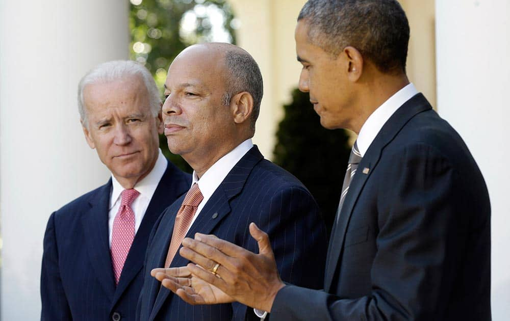 President Barack Obama stands with Jeh Johnson, his choice for the next Homeland Security Secretary, and Vice President Joe Biden in the Rose Garden at the White House in Washington.