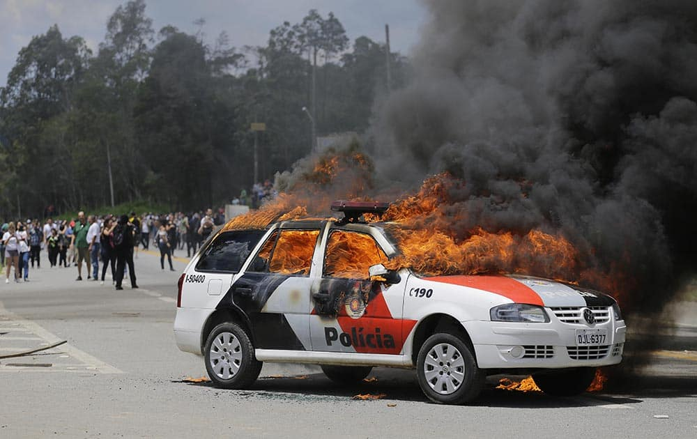 A police car burns after it was set on fire by demonstrators protesting drug testing on animals at the Instituto Royal laboratory in Sao Roque, Brazil.