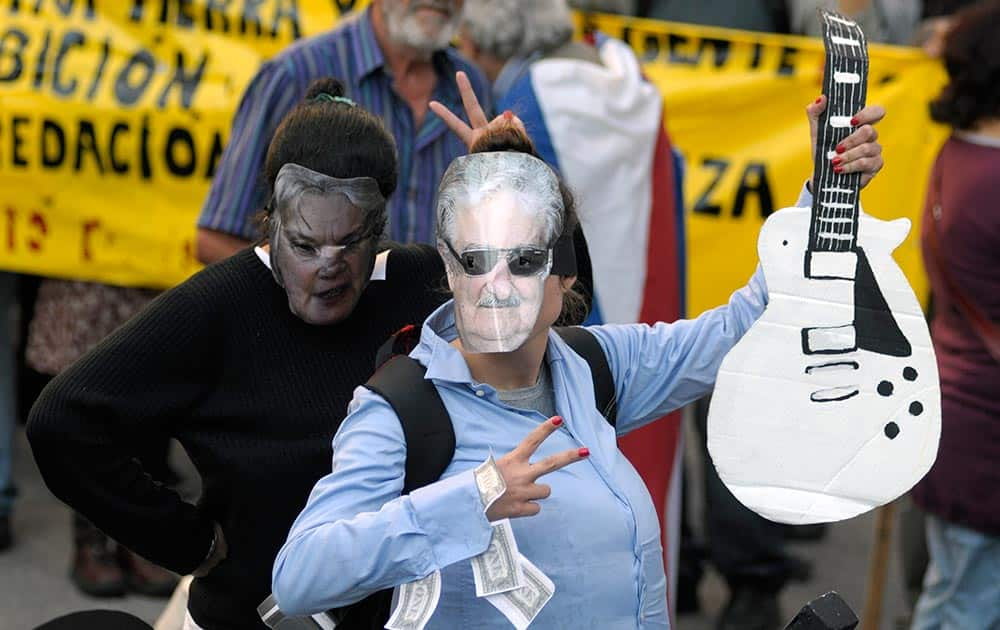 A protester wears a homemade mask depicting Uruguay`s President Jose Mujica holding a cardboard interpretation of the guitar given to the leader by Aerosmith frontman Steven Tyler.