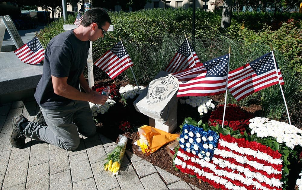 Tim Brignolo, of the Massachusetts Institute of Technology facilities department, waters the flowers at a temporary memorial to slain MIT police Officer Sean Collier in Cambridge, Mass.