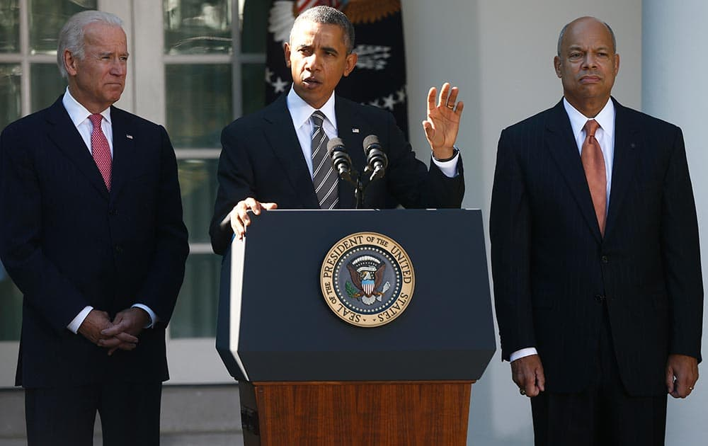President Barack Obama stands with Jeh Johnson, his choice for the next Homeland Security Secretary, and Vice President Joe Biden, in the Rose Garden at the White House in Washington.