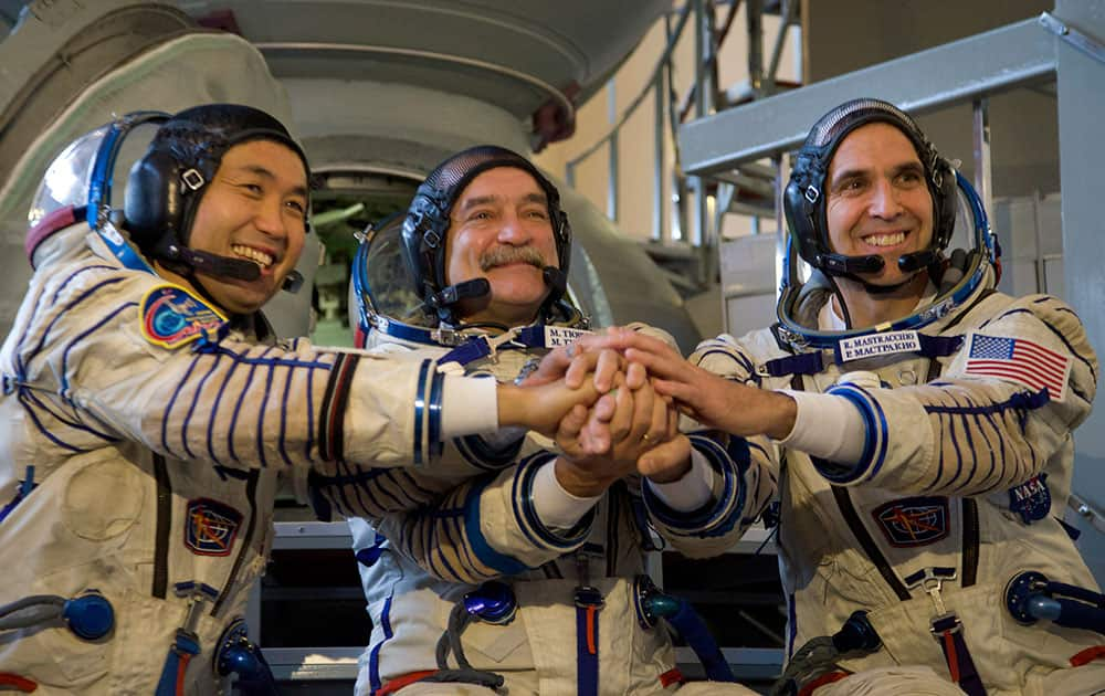 Japanese astronaut Koichi Wakata, Russian cosmonaut Mikhail Tyurin and NASA astronaut Rick Mastracchio shake hands before their final preflight practical examination in a mock-up of a Soyuz TMA space craft at Russian Space Training Center in Star City, outside Moscow, Russia.