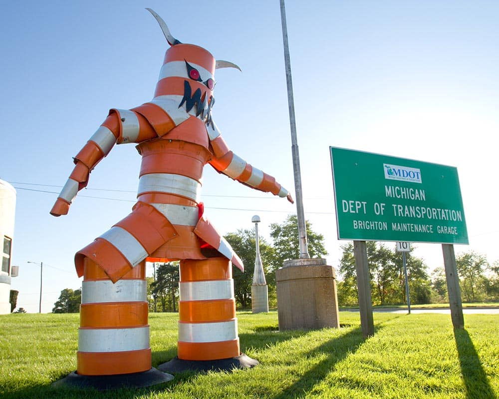 A monster constructed from traffic cones by garage workers looms over drivers passing along Grand River near Old U.S. 23 in front of the MDOT Brighton Maintenance Garage.