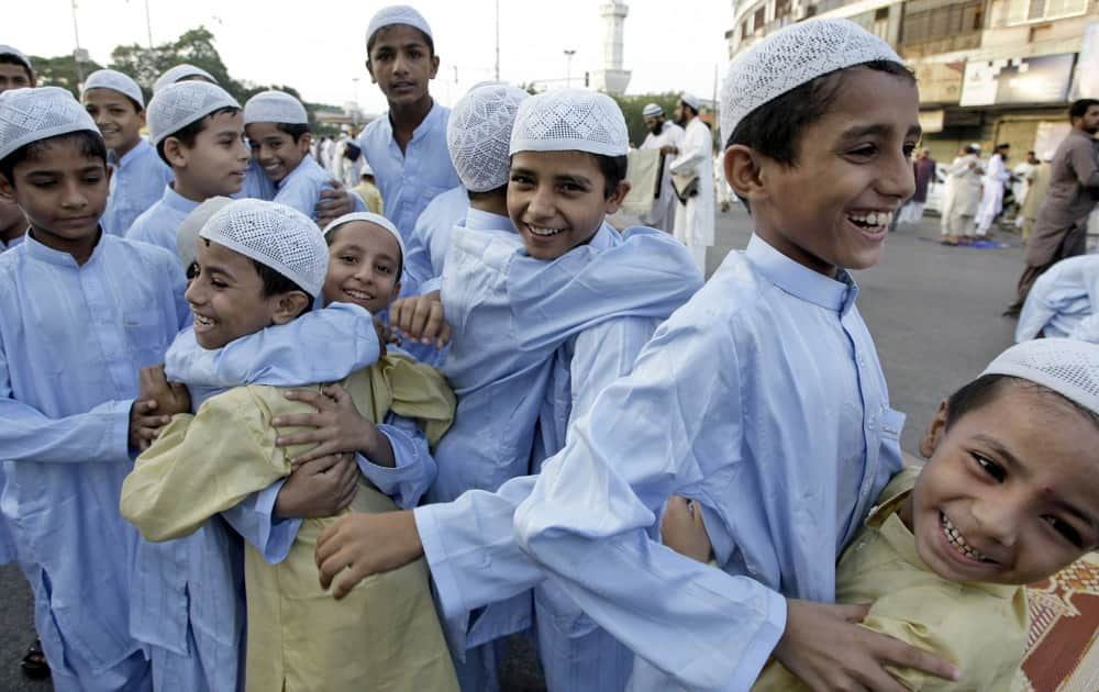 Pakistani boys greet each other after praying on the first day of the Muslim holiday of Eid al-Adha, or