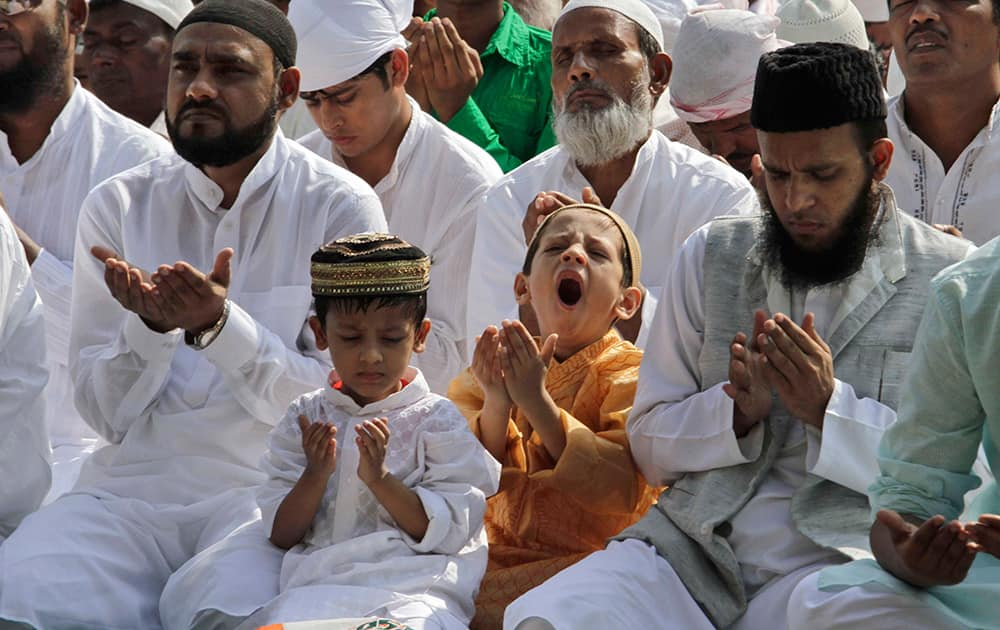 A boy yawns as Muslims offer prayers during Eid al-Adha, or the Feast of the Sacrifice, in Kolkata.