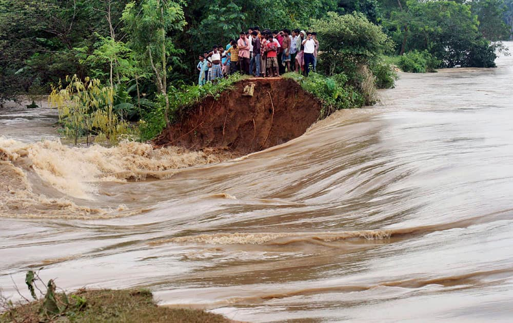 Villagers stand on the breached embankment of swollen Kangsabati river at Samat village in West Bengal state.