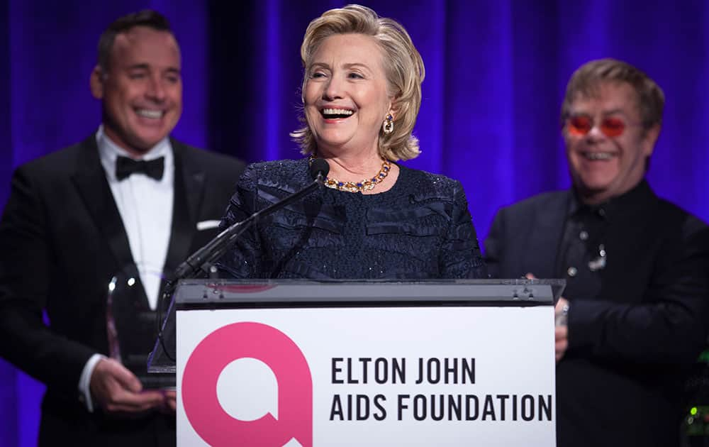 Former Secretary of State Hillary Clinton speaks as Elton John and his partner David Furnish look on, after receiving her Founders award during the Elton John AIDS Foundation`s 12th Annual