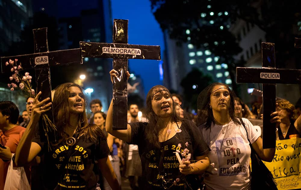 Striking teachers hold up crosses during a march on the nation`s teacher recognition day, in Rio de Janeiro, Brazil.