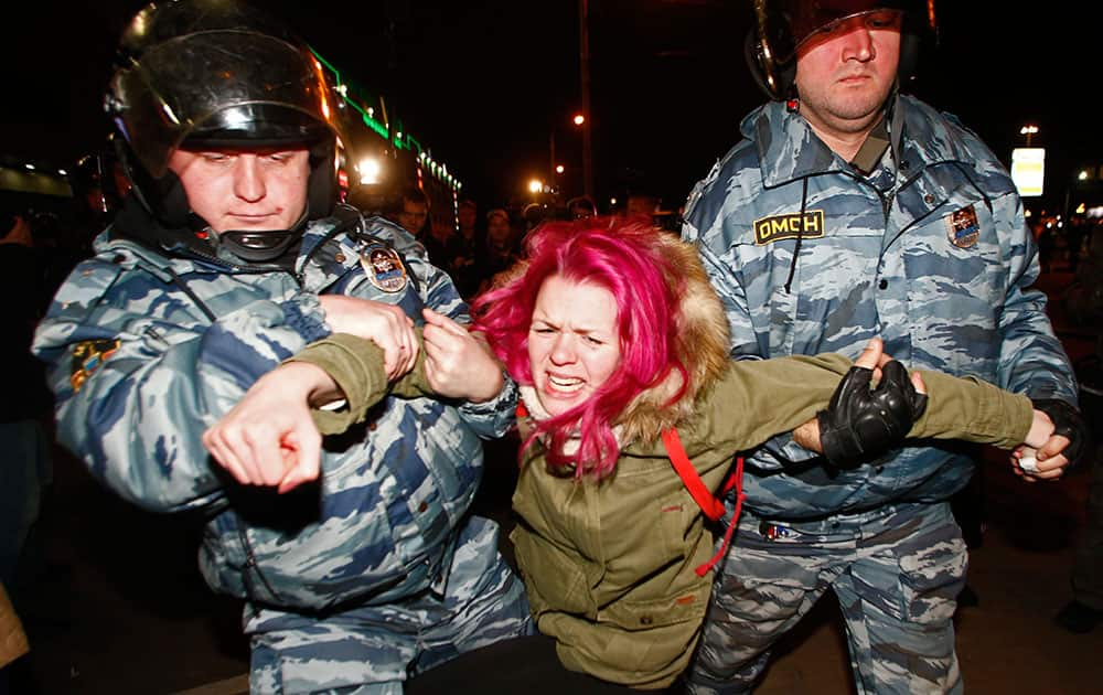 Police officers detain a protester in Moscow, Russia.