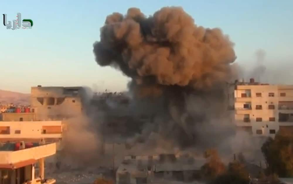 This image taken from video obtained from the Shaam News Network, which has been authenticated based on its contents and other AP reporting, smoke billows amid buildings at a bomb explosion in Daraya, a countryside of Damscus, Syria.