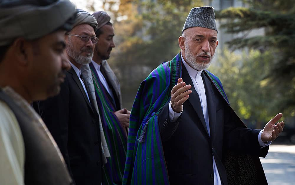 Afghan President Hamid Karzai arrives at a mosque inside the presidential palace to deliver his Eid al-Adha message, in Kabul, Afghanistan.