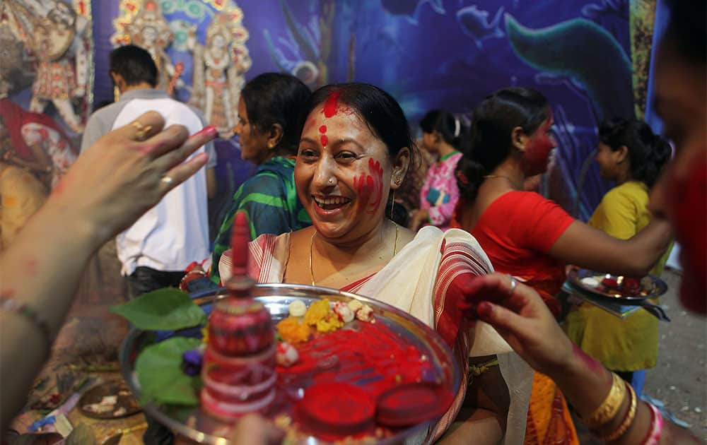 An Indian woman laughs as others prepare to apply vermilion on her on the last day of Durga Puja festivities in Gauhati, India.