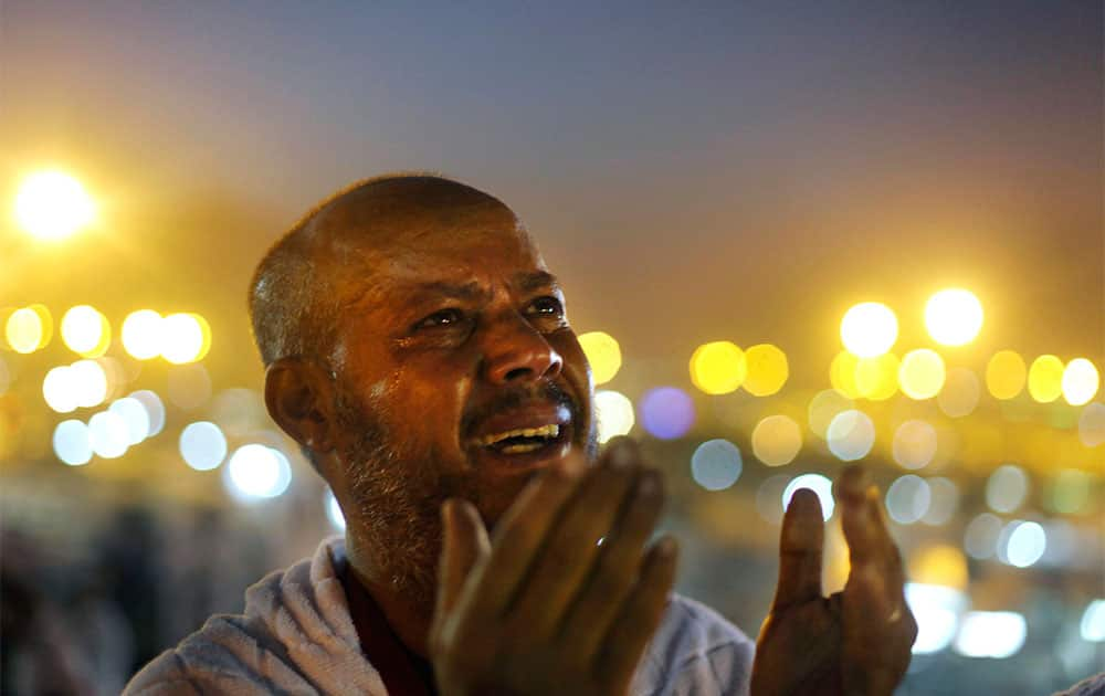 An Egyptian Muslim pilgrim cries as he prays at sunrise on a rocky hill called the Mountain of Mercy, on the Plain of Arafat near the holy city of Mecca, Saudi Arabia.