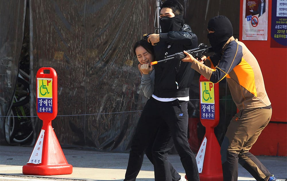 Mock terrorists threaten a hostage during an anti-terrorism exercise at a shopping center in Seoul, South Korea.