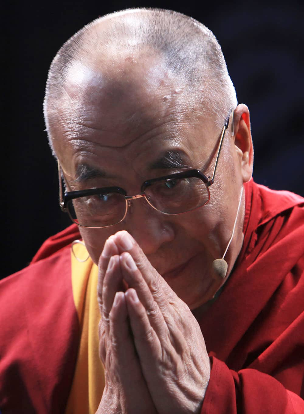 Tibet`s spiritual leader the Dalai Lama offers a greeting as he arrives during a ceremony at a theater in Mexico City.