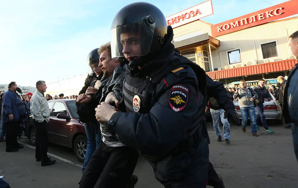 Police officers detain a protester in Moscow, Russia. The fatal stabbing of an ethnic Russian man has ignited anger in Moscow against people from the Caucasus, with demonstrators breaking into a shopping center and storming a vegetable warehouse Sunday evening.