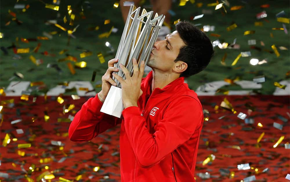 Serbia`s Novak Djokovic kisses his trophy during the award ceremony of the Shanghai Masters tennis tournament at Qizhong Forest Sports City Tennis Center.
