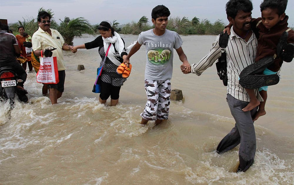 People hold each others` hands and cross a water logged road as they return to their respective villages near Gopalpur, Orissa state.