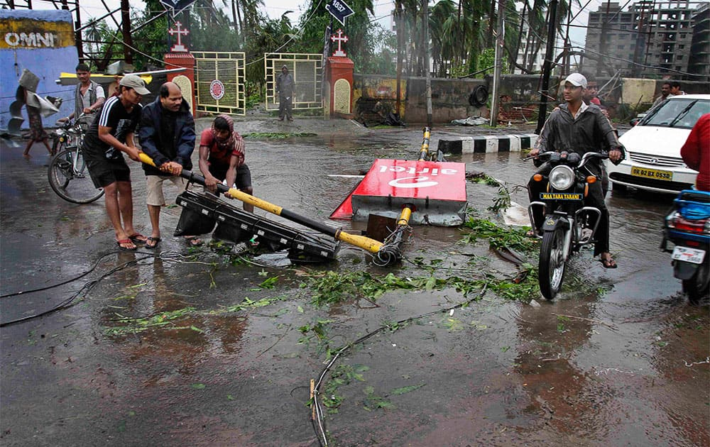 Locals remove a traffic signal pole fallen during Cyclone Phailin from a road in Berhampur.