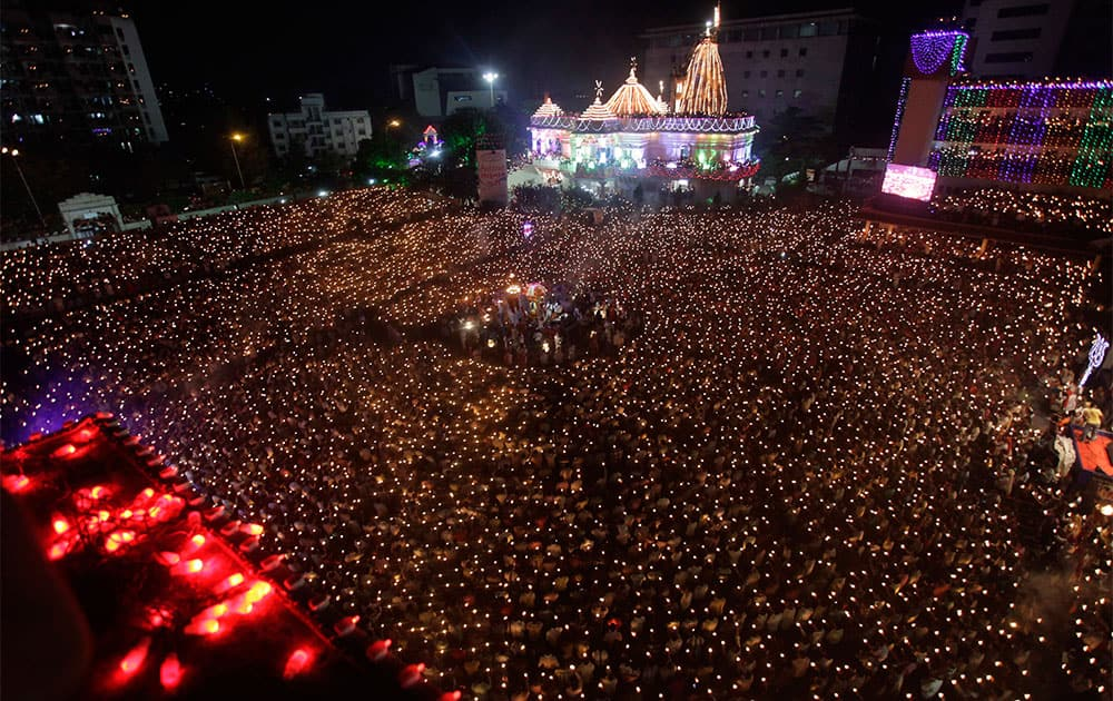 Indian devotees hold earthen lamps and candles as they take part in the Maha Aarti ritual at Hindu deity Umiya Mata temple on the eighth night of Navratri in Surat.