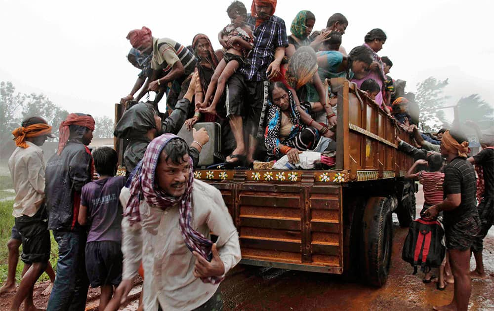 Evacuated Indian villagers get down from a truck at a relief camp as it rains near Berhampur.