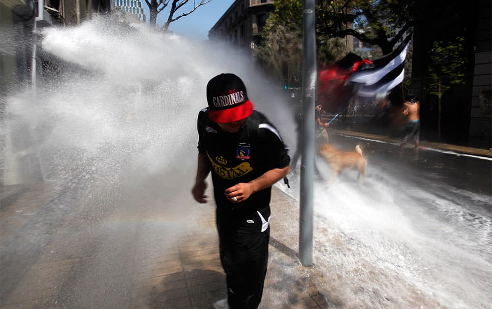 A protester runs away from a police water cannon after clashes broke out at a march against the commemoration of the discovery of America in Santiago, Chile.