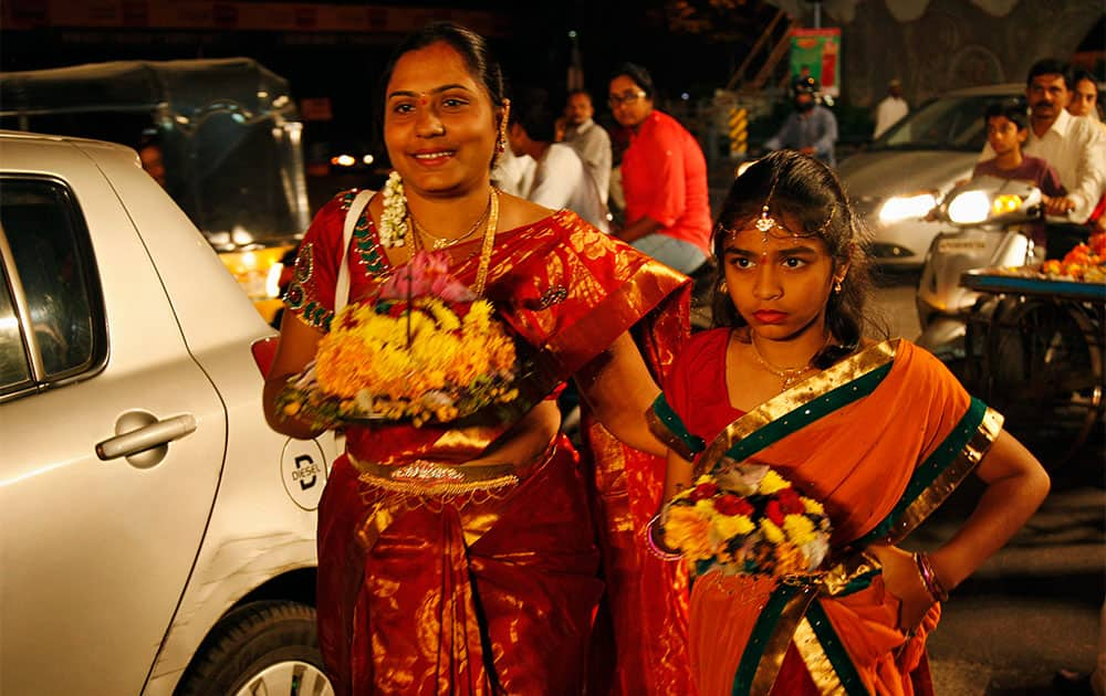 An Indian woman carries Bathukammas, floral arrangement representing the giver of life, during the Bathukamma festival dedicated to the Hindu Goddes Gauri in Hyderabad.