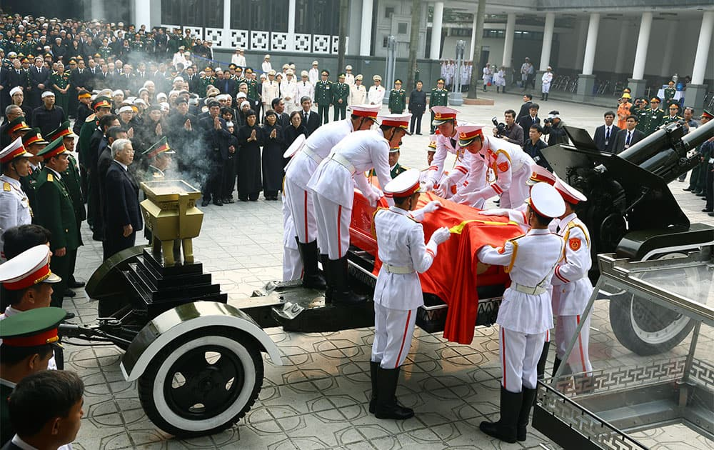 Members of a Vietnamese honor guard place the national flag on the late Gen. Vo Nguyen Giap`s coffin during his funeral at the National Funeral House in Hanoi, Vietnam.