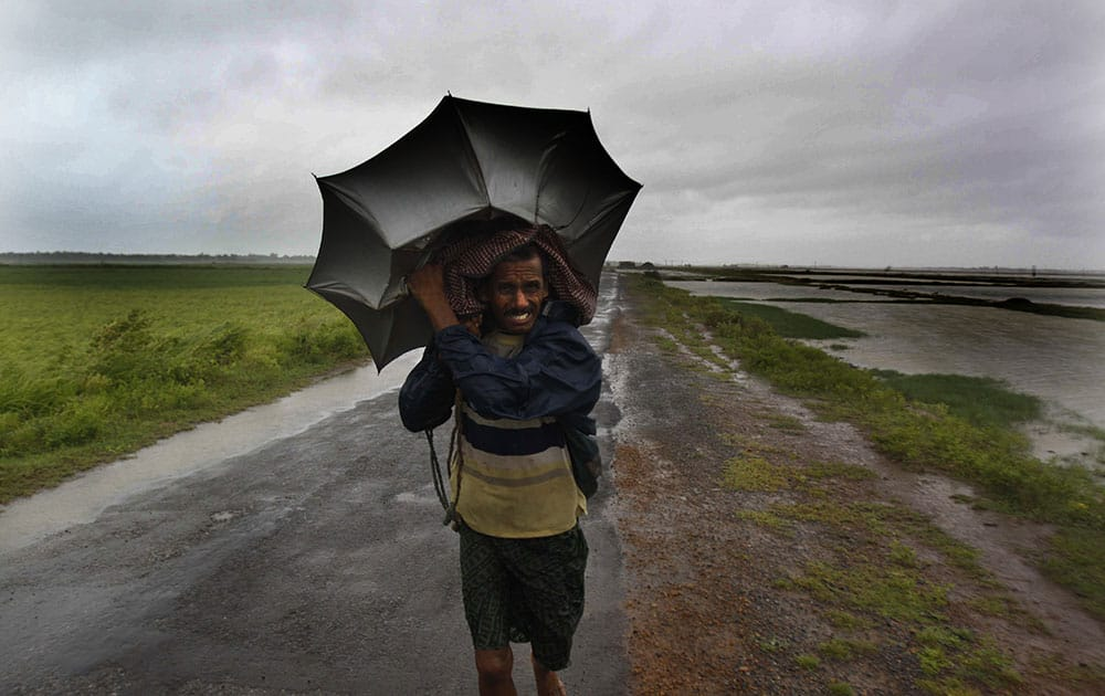 A villager braving strong winds and rain walk to a safer place, in village Podampeta, in Ganjam district about 200 kilometers from the eastern Indian city Bhubaneswar.