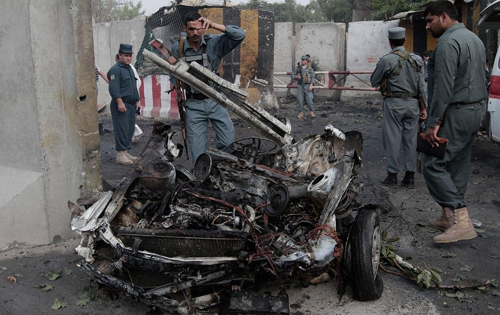 Afghan police examines the remains of a car after a suicide bomber attacked a police headquarters in Jalalabad east of Kabul, Afghanistan.
