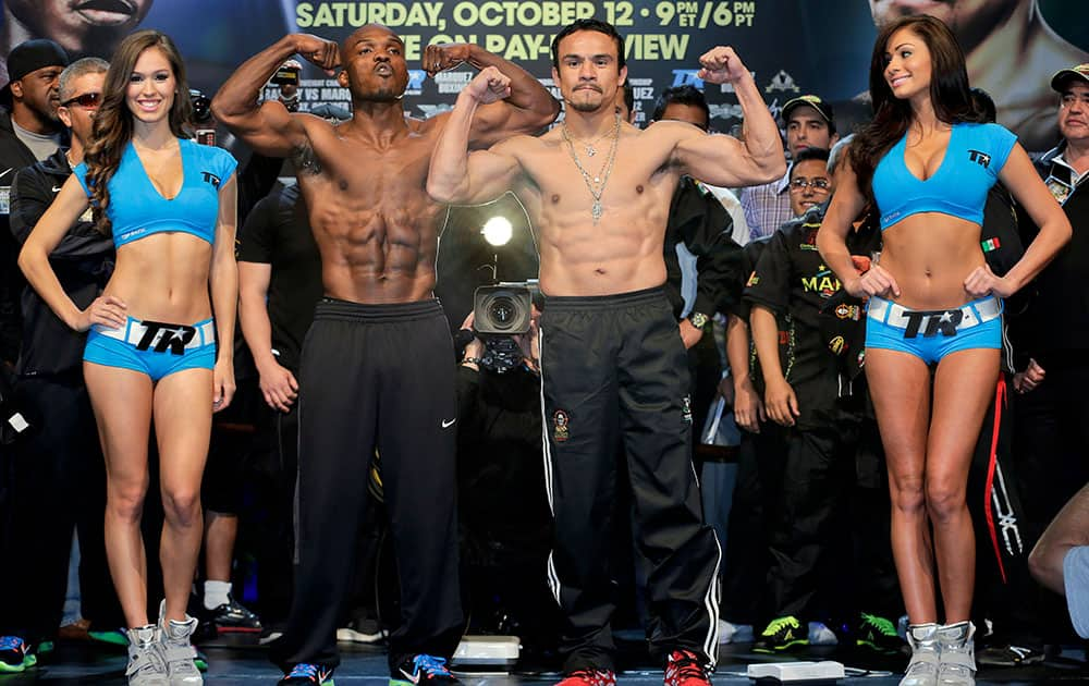 Timothy Bradley and Juan Manuel Marquez pose for photos after the weigh-in for their Saturday WBO welterweight title fight, in Las Vegas.