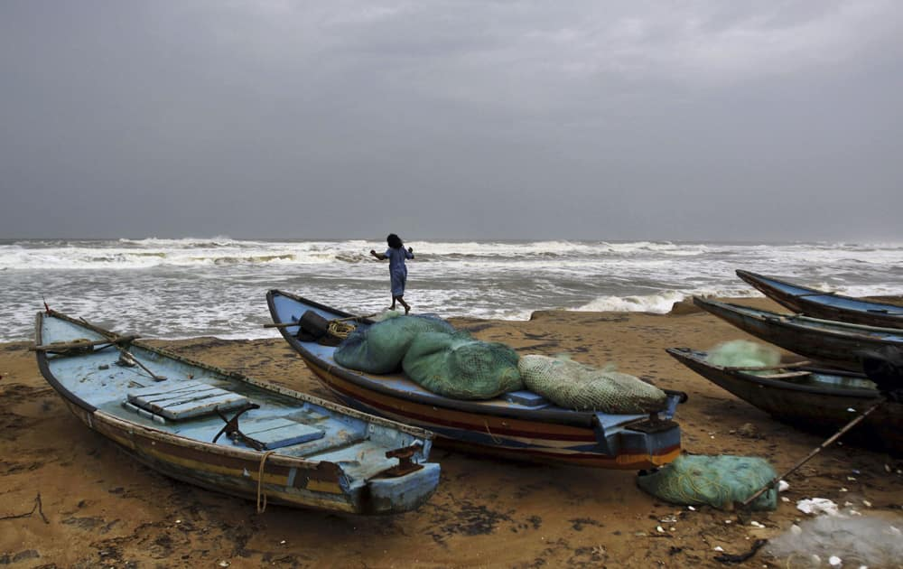 A young Indian girl plays on top of an anchored boat at the Bay of Bengal coast in Gokhurkuda in Ganjam district 215 kilometers (136 miles) away from the eastern Indian city of Bhubaneswar.