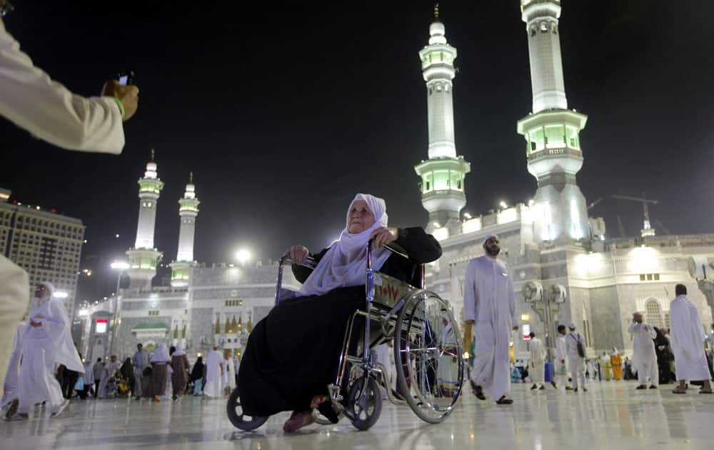 An elderly Muslim pilgrim poses for a picture in front of the Grand Mosque in the holy city of Mecca, Saudi Arabia.