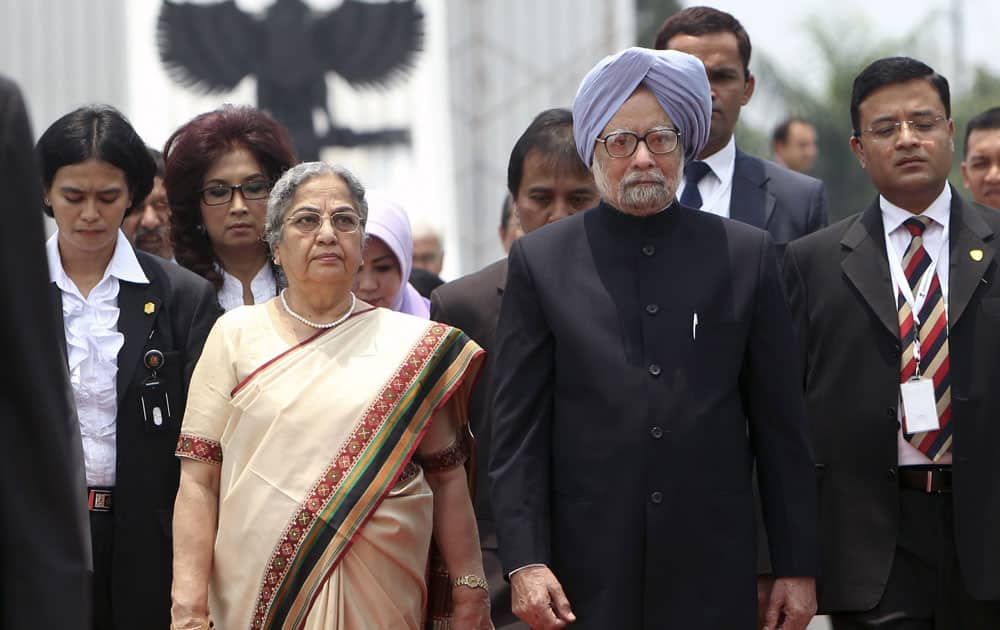 Prime Minister Manmohan Singh, walks with his wife Gursharan as they leave a wreath laying ceremony at Kalibata Heroes Cemetery in Jakarta, Indonesia.