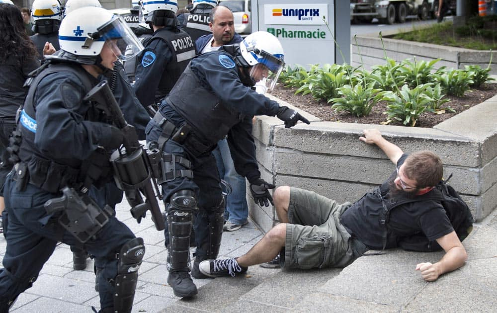Police disperse protestors during a demonstration near the site of hearings for a pipeline project, in Montreal.