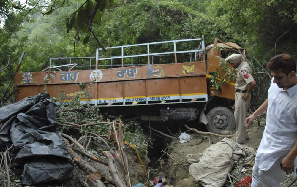 A policeman inspects the wreckage after a truck carrying Hindu pilgrims crashed into a gorge in Hoshiarpur, a town 380 kilometers north of New Delhi. Police say at least 20 people were killed and another 35 injured in the accident.