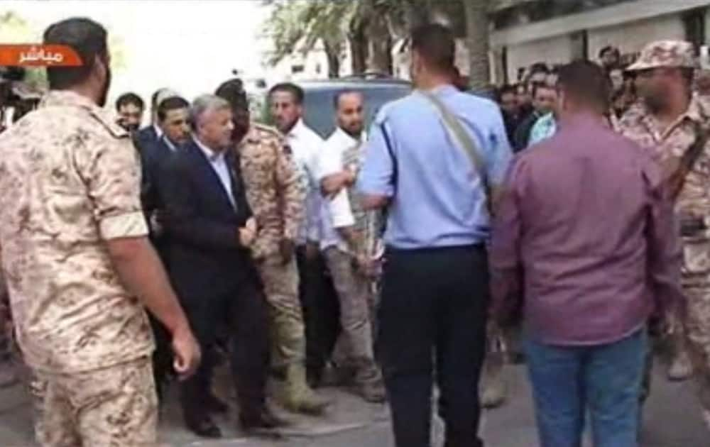 Libyan Prime Minister Ali Zidan appears on a Libyan TV as he arrives at his cabinet office in the capital, Tripoli, Libya. Zidan has appeared in public for the first time since his release after being abducted by gunmen from his hotel earlier in the day.
