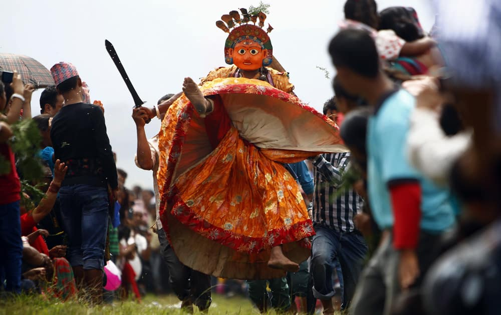 Nepalese devotees carry a dancer wearing a mask of a deity as he performs during Shikali festival in Khokana, Lalitpur, Nepal.
