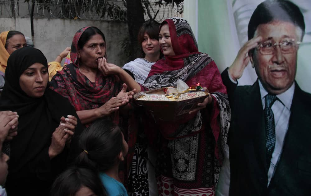 Supporters of former Pakistan President Pervez Musharraf, celebrate the news that a court has granted bail to their leader by exchanging sweets, in Islamabad.