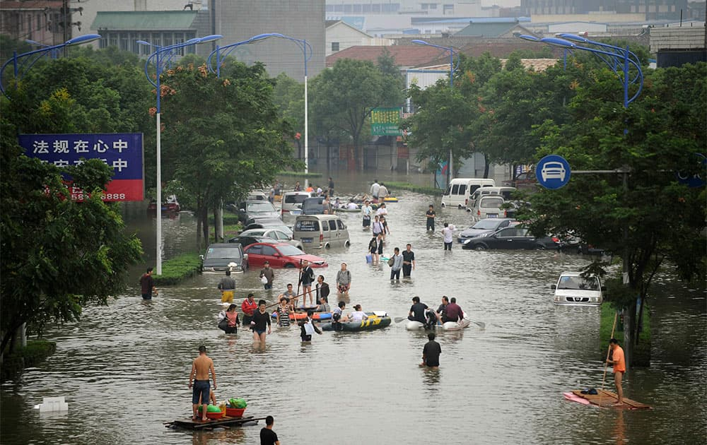 People wade through a flooded street in Yuyao, in east China`s Zhejiang province.