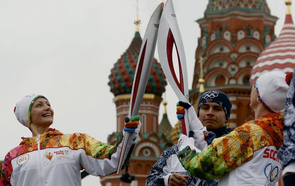 Russian Olympic gold medalists, synchronized swimmer Anastasya Davydova and former artistic gymnast Svetlana Khorkina, join their torches during a relay of the Olympic flame in Moscow.