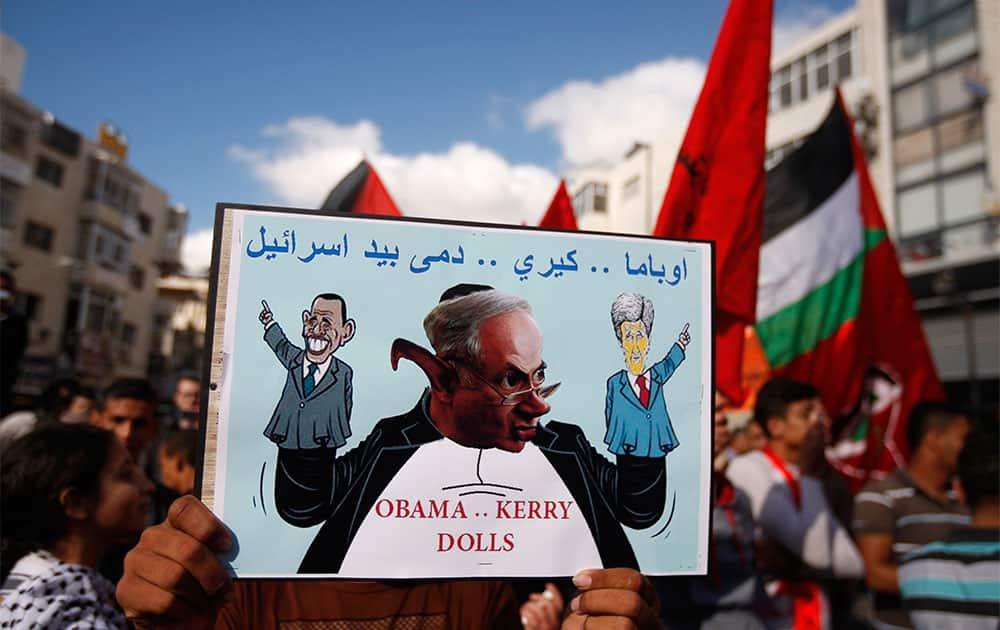 A Palestinian protester holds up a poster with a caricature of US Secretary of State John Kerry during a protest against the resuming of the peace talks with Israel, in the West Bank city of Ramallah.