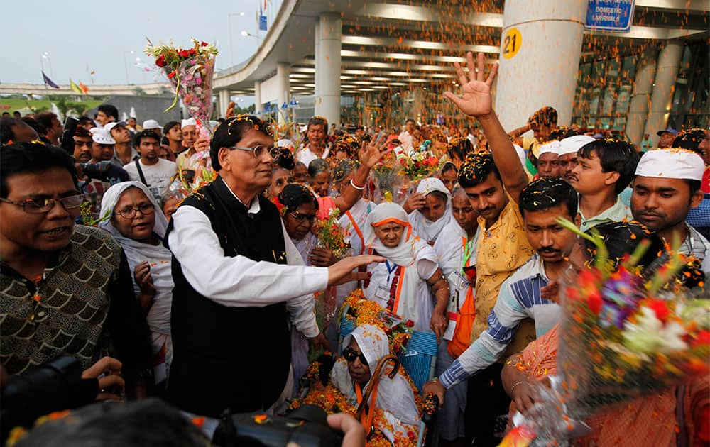 A group of widows from the north Indian town Vrindavan who are being taken on a trip to Kolkata by non-governmental organization Sulabh International, are showered with flower petals by Sulabh founder Bindeshwar Pathak, centre, as he welcomes them in Kolkata.