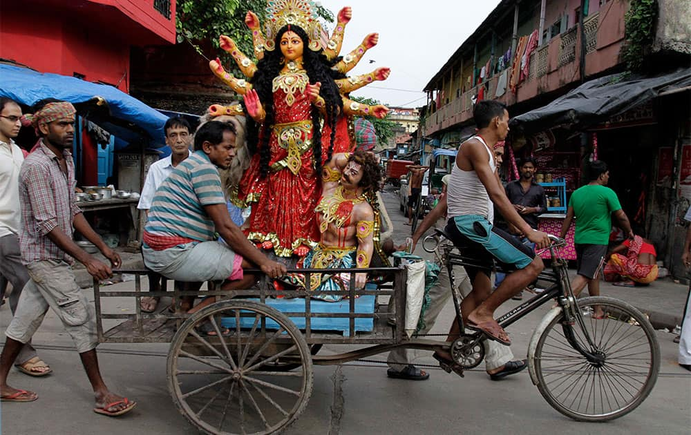 An idol of Hindu goddess Durga is transported on a cycle rickshaw to a venue of worship in Kolkata.