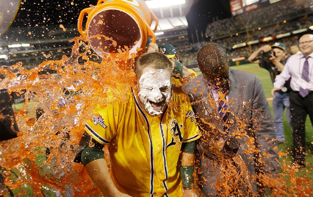 Oakland Athletics` Stephen Vogt gets a Gatorade shower after making the game-winning hit to beat the Detroit Tigers 1-0 in Game 2 of the American League baseball Division Series in Oakland, Calif.