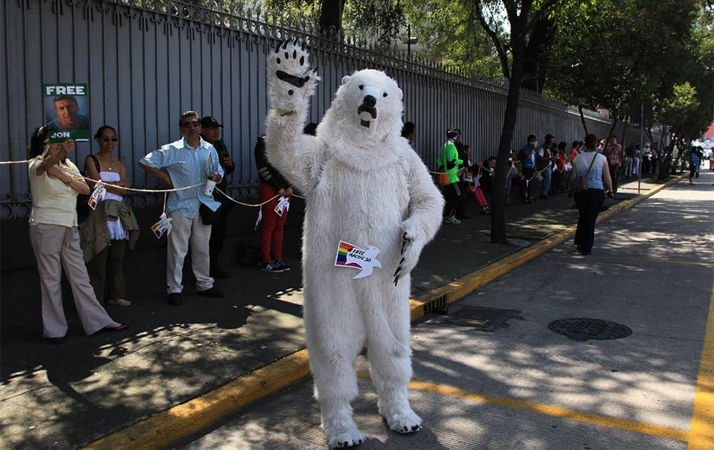 A Greenpeace activist wearing a polar bear costume waves during a demonstration in front of the Russian embasssy in Mexico City.