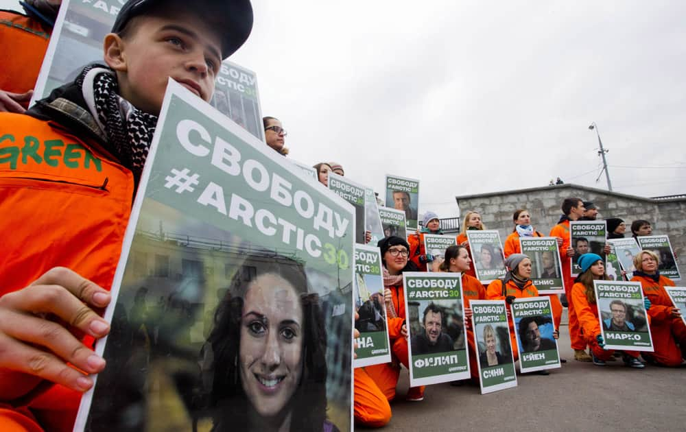 Greenpeace activists hold up portraits of the seized crew members of the ship
