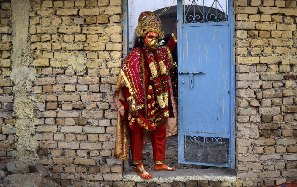 A Hindu man dressed up like God Hanuman waits to participate in a religious procession of Navratri festival in Amritsar.