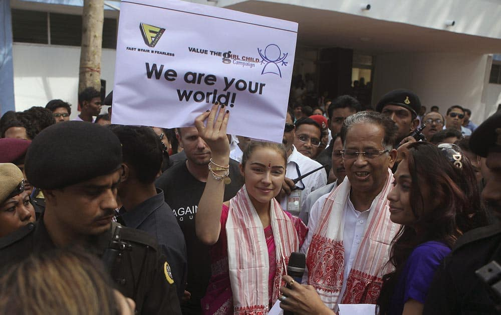Miss Universe Olivia Culpo, holds a placard as she stands with Assam state Chief Minister Tarun Gogoi, during a campaign
